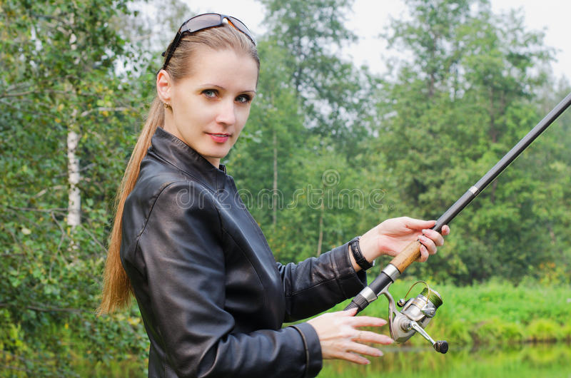 Den härliga unga kvinnan på fiske arkivfoton