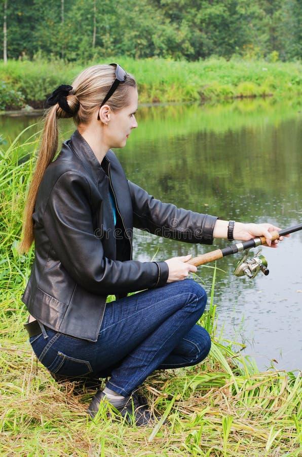 Den härliga unga kvinnan på fiske royaltyfria foton