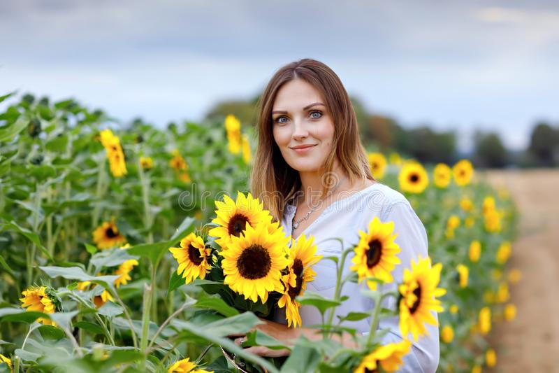 Den härliga unga kvinnan på solrosfält med buketten blommar Lycklig flicka på sommarsolnedgångdag royaltyfri fotografi