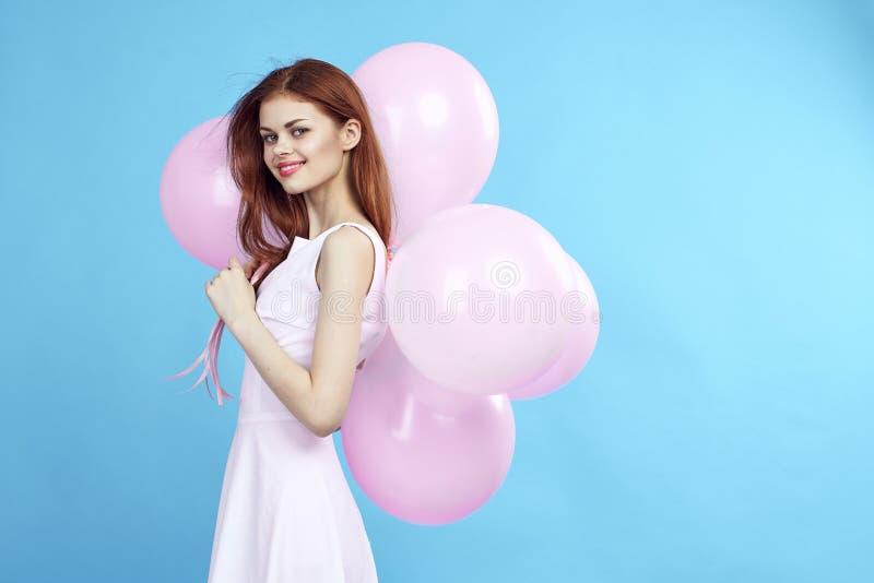 Den härliga unga kvinnan rymmer ballonger på en blå bakgrund, tomt utrymme för kopia fotografering för bildbyråer