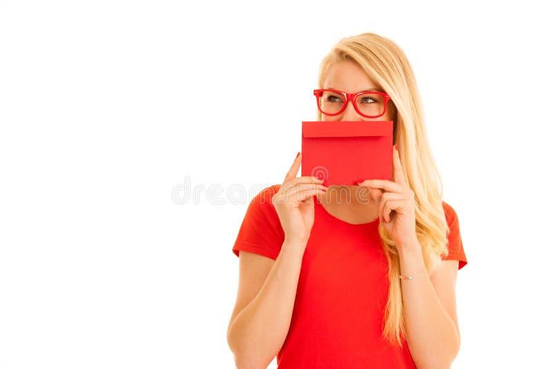 Den härliga unga kvinnan rymmer det röda kuvertet - en förälskelsebokstav för va royaltyfri foto