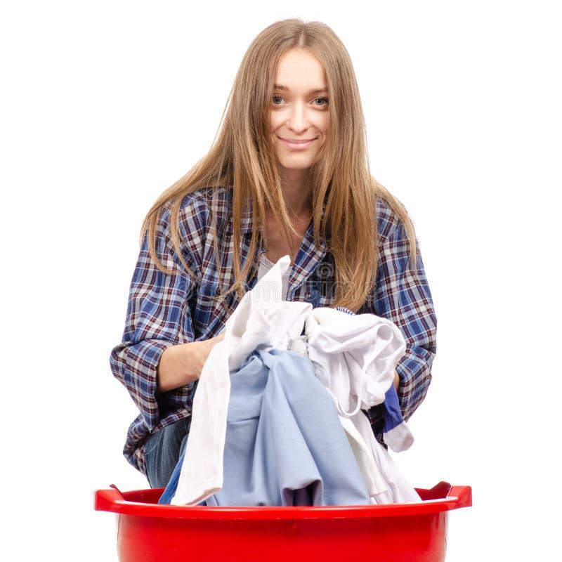 Den härliga unga kvinnan rymmer en handfat med att le för tvätteri arkivfoto