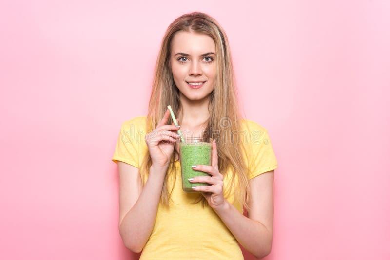 Den härliga unga kvinnan rymmer den gröna smoothien med sugrör och att le nära den rosa väggen royaltyfri fotografi