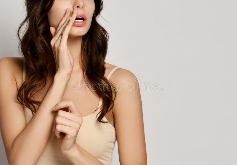 Den härliga unga kvinnan rymmer hennes arm på munnen, som hon talar något i en viskning arkivfoto