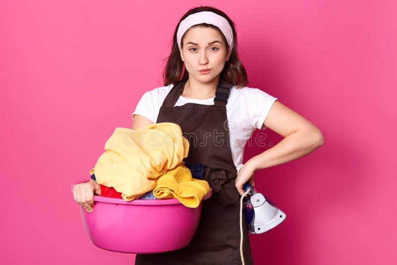 Den härliga unga kvinnan rymmer den rosa handfatet med tvätterit och järn som ser kameran, medan stå isolerad över rosa bakgrund, arkivfoton