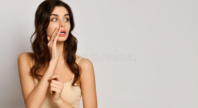 Den härliga unga kvinnan ser åt sidan på utrymme för fri text och rymmer hennes arm på munnen, som hon talar något i en viskning arkivbild