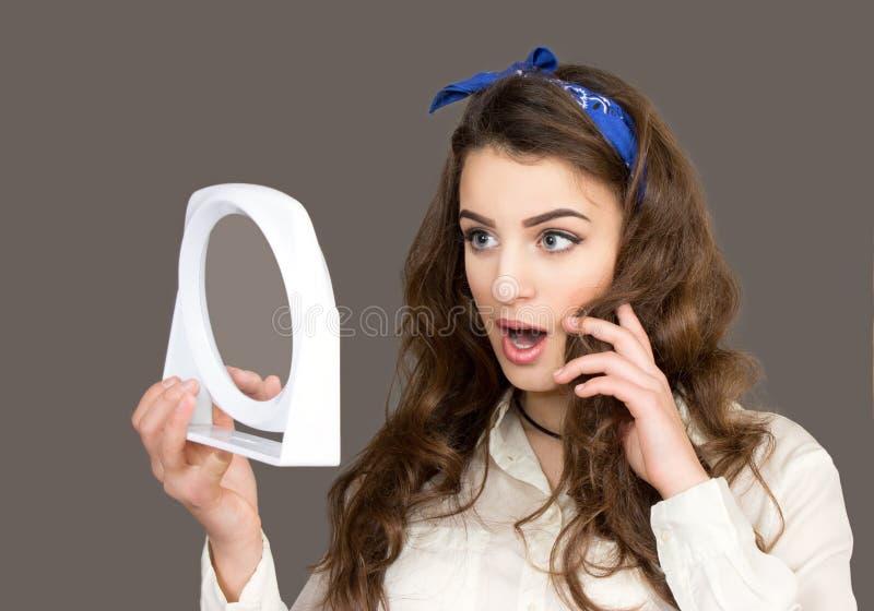 Den härliga unga kvinnan ser i en spegel royaltyfri foto