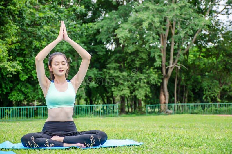 Den härliga unga kvinnan sitter meditationen som gör yoga parkerar in Att koppla av och att meditera, medan omges, i sommar parke royaltyfria bilder