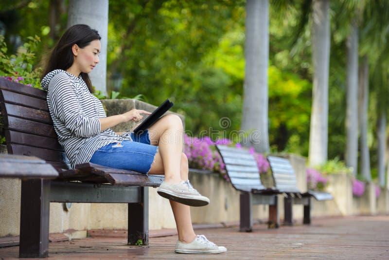 Den härliga unga kvinnan som använder minnestavladatoren på en bänk i, parkerar royaltyfria bilder