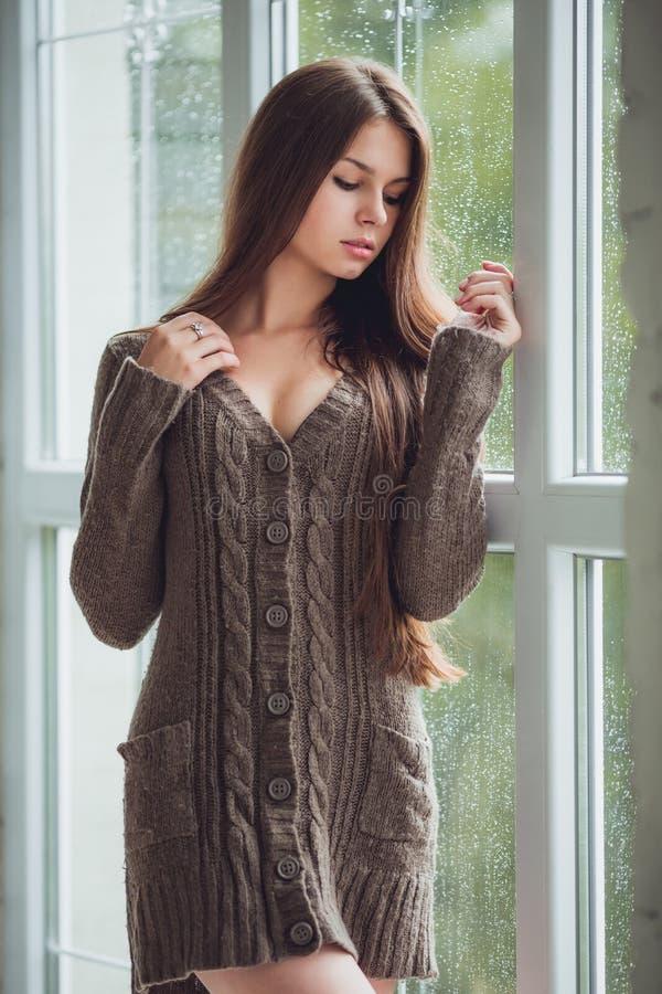 Den härliga unga kvinnan som bara står fönstret med regn, tappar nästan Sexig och ledsen flicka Begrepp av ensamhet arkivbild