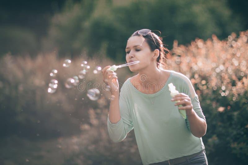 Den härliga unga kvinnan som blåser såpbubblor i, parkerar soligt arkivbild