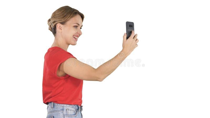 Den härliga unga kvinnan som går och rymmer en smartphone tar upp till, bilder och selfies på vit bakgrund arkivbilder