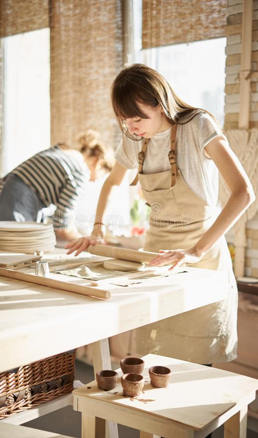 Den härliga unga kvinnan som gör keramik, rullar ut med en kavel i solljus Begrepp för kvinnan i frilans-, affär, arkivbild