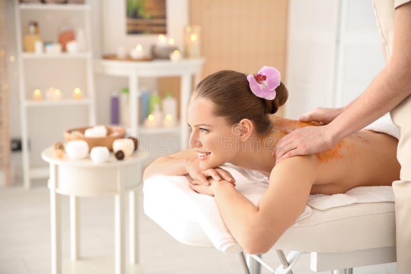 Den härliga unga kvinnan som har massage med kroppen, skurar royaltyfria foton