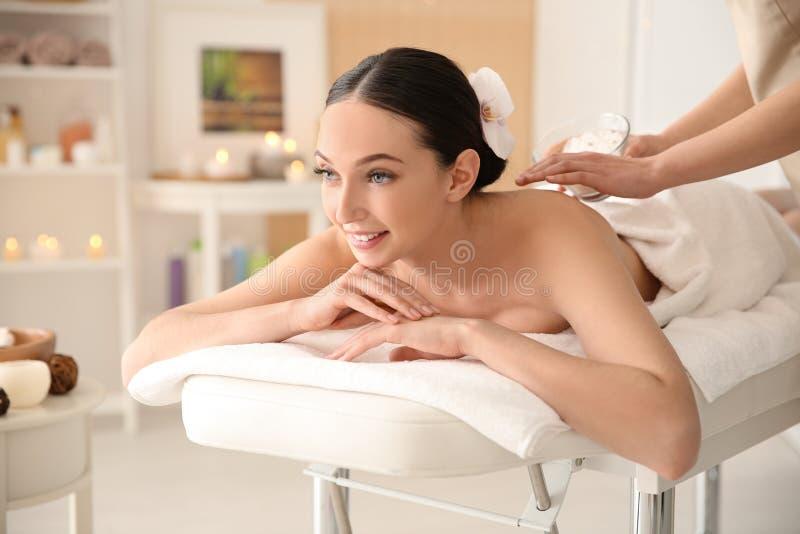 Den härliga unga kvinnan som har massage med kroppen, skurar royaltyfri foto
