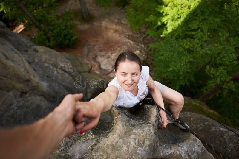 Den härliga unga kvinnan som klättrar på, vaggar utomhus i sommar Top besk?dar Den lyckliga flickaklättringen vaggar trekking det royaltyfria foton