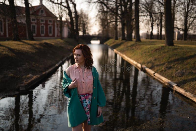 Den härliga unga kvinnan som kopplar av nära en kanalflod i, parkerar nära slotten i Rundale, Lettland, 2019 arkivfoton