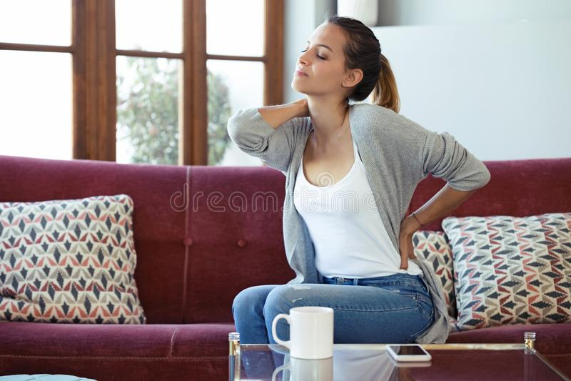 Den härliga unga kvinnan som lider från baksida, smärtar, medan sitta på soffan hemma arkivfoto