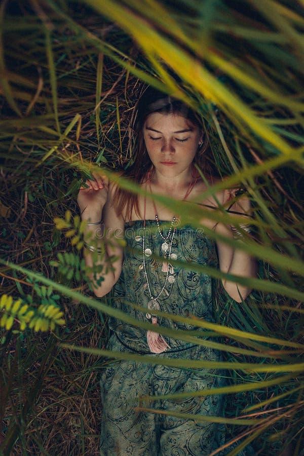Den härliga unga kvinnan som ligger på gräset med ögon, stängde sig Överkant v fotografering för bildbyråer
