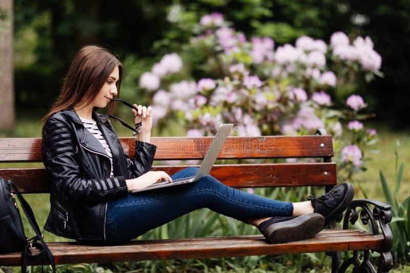 Den härliga unga kvinnan som offentligt sitter, parkerar att prata över bärbar datordatoren parkerar in royaltyfria bilder