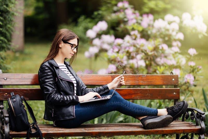 Den härliga unga kvinnan som offentligt sitter, parkerar att prata över bärbar datordatoren parkerar in arkivfoton