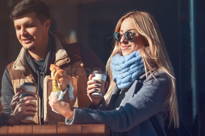 Den härliga unga kvinnan som tycker om hennes lunchgiffel med kaffe medan hon som utomhus står kafét och, meddelar med vänner royaltyfri bild