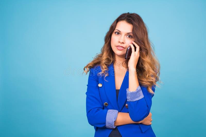 Den härliga unga kvinnan talar samtal vid mobiltelefonen på en blå bakgrund royaltyfri fotografi