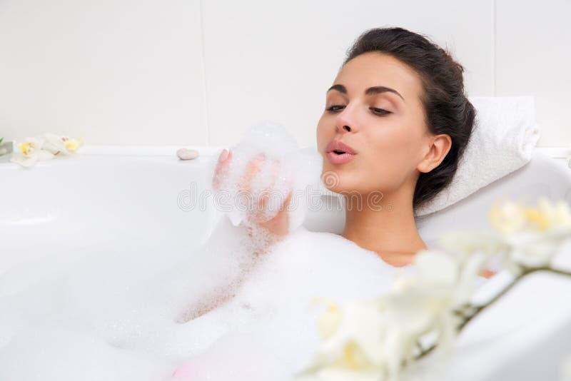 Den härliga unga kvinnan tar bubbelbadet fotografering för bildbyråer