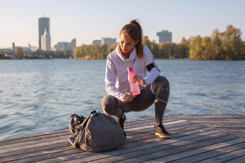 Den härliga unga kvinnan tröttade, når han har utarbetat utvändig dricka w fotografering för bildbyråer