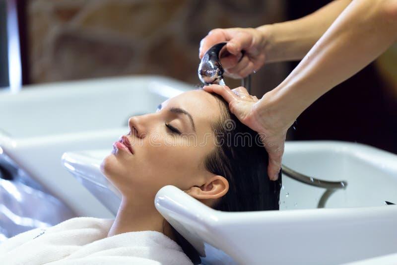 Den härliga unga kvinnan tvättar hår i en skönhetsalong royaltyfri foto