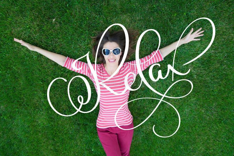 Den härliga unga kvinnan tycker om naturen Den sunda le flickan i bokstäverord för grönt gräs och kalligrafikopplar av fotografering för bildbyråer
