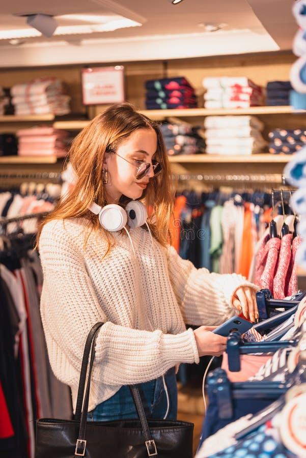 Den härliga unga kvinnan väljer kläder på mode, och kläder shoppar royaltyfri bild