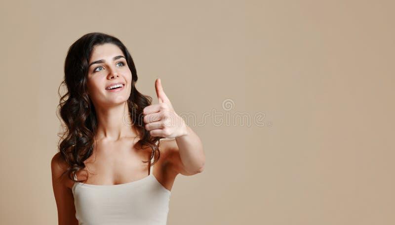 Den härliga unga kvinnan visar upp tummen, rymmer handen på höft, skrattar och ser kameran royaltyfria bilder