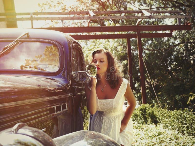 Den härliga unga kvinnlign fixar hennes smink nära tappningbilen royaltyfri fotografi