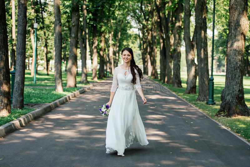 Den härliga unga le brunettbruden i weddklänning med buketten av blommor i händer går i parkera utomhus arkivbilder