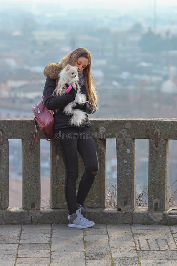 Den härliga unga le flickan strosar med den lilla vita hunden Tysk dvärg- Spitz pomeranian royaltyfria bilder