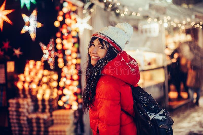 Den härliga unga le kvinnan tycker om snövintertid på julmässa i bärande hatt för nattstad och rött omslag royaltyfri fotografi