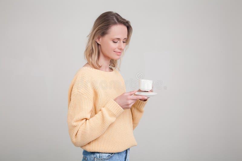 Den härliga unga mjuka flickan med blont hår som står med en kopp kaffe i hennes händer, är hon iklädd en gul tröja poserar royaltyfri bild