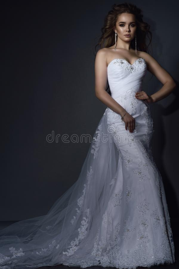Den härliga unga modellen med perfekt utgör, och blåsa hår som bär den vita lyxiga sjöjungfrun, snöra åt bröllopsklänningen med d royaltyfri fotografi