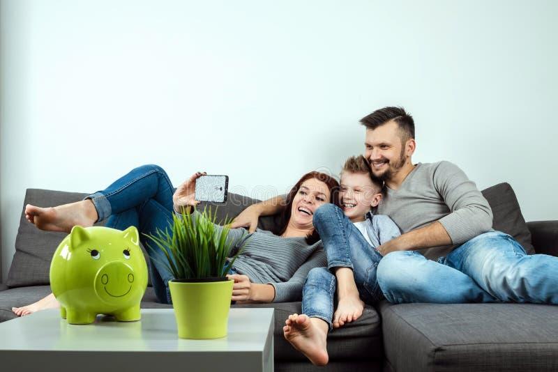 Den härliga unga modern, fadern och en son gör selfie genom att använda en telefon och le, medan sitta på soffan hemma Lyckligt arkivbild