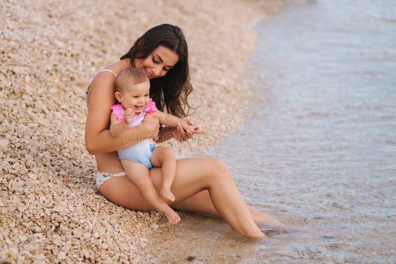 Den härliga unga modern med hennes gulligt behandla som ett barn flickan som tycker om sommarsolen på stranden Lyckliga flickor i royaltyfri foto