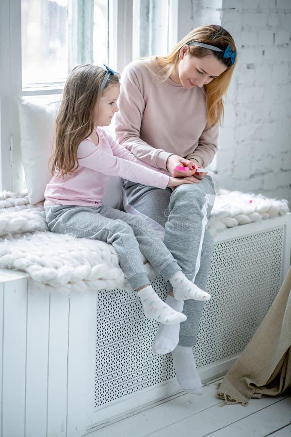 Den härliga unga modern och hennes lilla dotter sitter vid fönstret tillsammans, och att måla som är deras, spikar Moderlig omsor royaltyfri foto