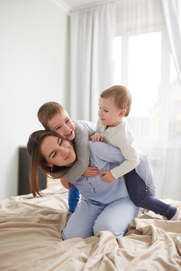 Den härliga unga modern och hennes två iklädda pyjamas för små söner har gyckel på sängen i det ljusa hemtrevliga sovrummet arkivfoto