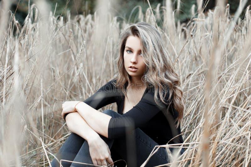 Den härliga unga nätta kvinnablondinen i stilfull jeans i en trendig svart skjorta vilar royaltyfria bilder