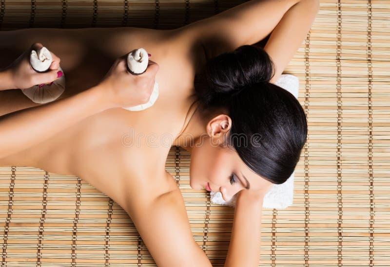 Den härliga, unga och sunda kvinnan på bambu som är matt i brunnsortsalong, har massage arkivbild