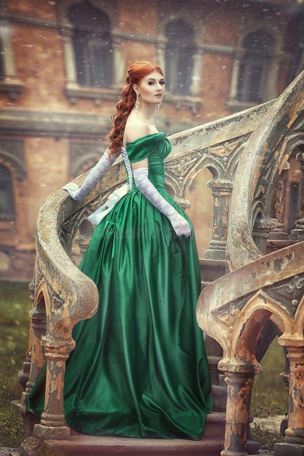 Den härliga, unga rödhåriga flickan i en grön medeltida klänning, klättrar trappan till slotten Fantastisk photosession fotografering för bildbyråer