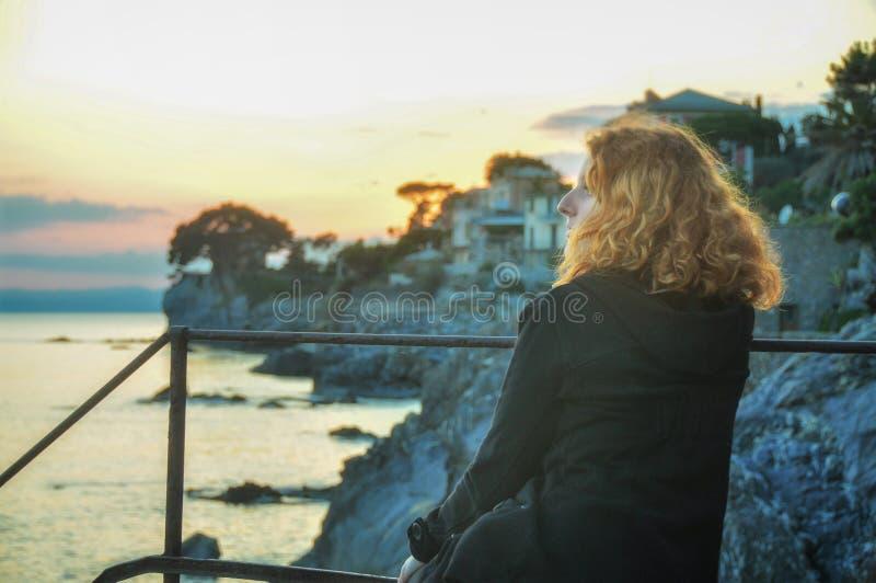 Den härliga unga rödhåriga kvinnan, på sjösidan i fiskeläget i Liguria, Italien tycker om solnedgången royaltyfria bilder