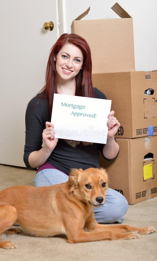 Den härliga unga redhaired kvinnan sitter med den flyttningaskar och hunden fotografering för bildbyråer