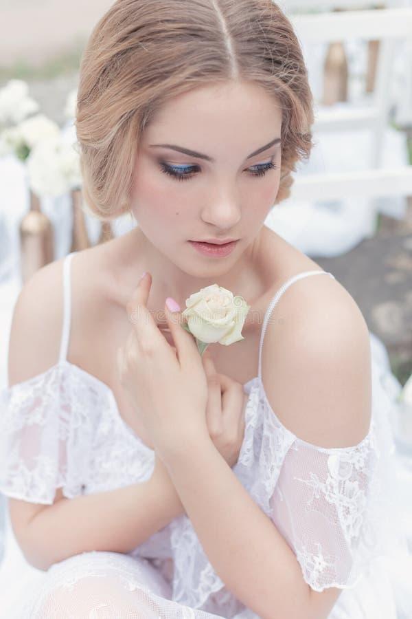 Den härliga unga söta blonda flickan med bröllopbuketten i händerna av budoar i en vit klänning med aftonfrisyren går fotografering för bildbyråer