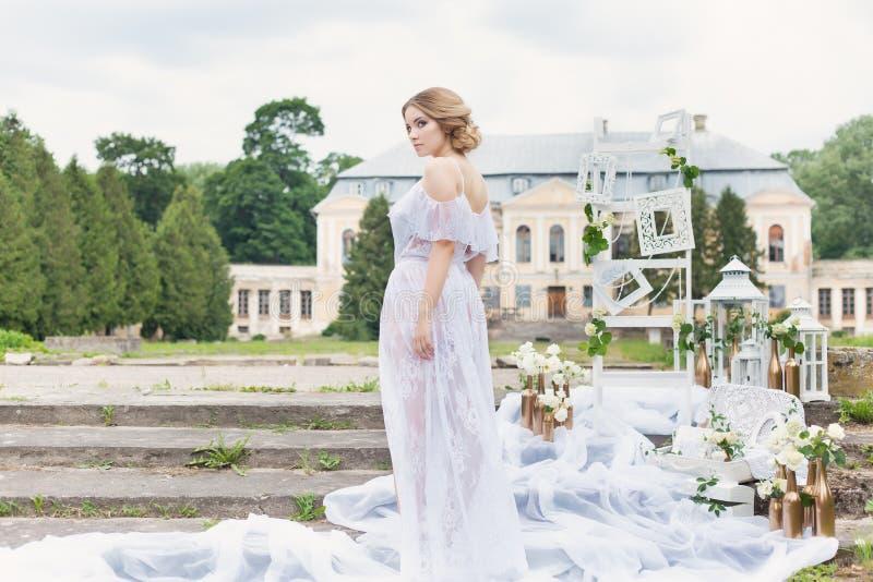 Den härliga unga söta blonda flickan med bröllopbuketten i händerna av budoar i en vit klänning med aftonfrisyren går royaltyfria bilder